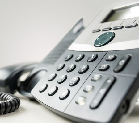 Close up angled view of a landline telephone instrument with a number pad and the handset or receiver off the hook in a communications concept.